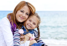 Two sisters at the beach in sunny autumn day Royalty Free Stock Photo