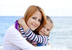 Two sisters at the beach in sunny autumn day Stock Photos