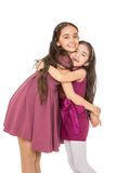 Two sisters in a beautiful fashion dresses hugging Stock Image