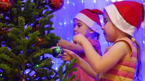 Two sisters beautiful girls decorate a Christmas tree with toys and garlands. Two beautiful girls decorate a Christmas tree with toys and garlands stock video