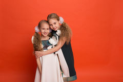 Two sisters in beautiful stylized dresses on a red background in Royalty Free Stock Image