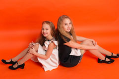 Two sisters in beautiful stylized dresses on a red background in. The studio. Two blonde girls posing in studio royalty free stock photo