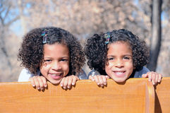 Two sisters on bench. A cute view of two multi-racial sisters grinning as they peek over the back of a wooden park bench stock photos