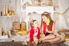 Two sisters with a big lollypop. Christmas time Royalty Free Stock Image