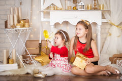 Two sisters with a big lollypop. Christmas time Royalty Free Stock Photography