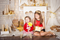 Two sisters with a big lollypop. Christmas time Stock Photo