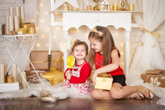 Two sisters with a big lollypop. Christmas time Royalty Free Stock Photos
