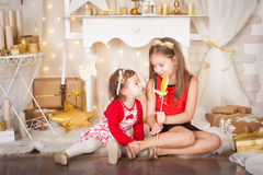 Two sisters with a big lollypop. Christmas time Stock Images