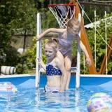 Two sisters in bikini near swimming pool. Hot Summer Stock Photos