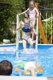 Two sisters in bikini near swimming pool. Hot Summer Stock Image