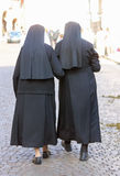 Two sisters with black dresses and a veil walking in the city Stock Photo