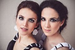 Two sisters with black and white fantasy make-up. Vogue style photo of two ladies in black and white long dresses with fantasy make-up Royalty Free Stock Photography