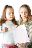 Two sisters with blank paper Royalty Free Stock Photo