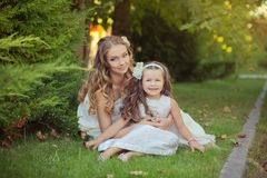 Two sisters blond chestnut blue eyes lady girls posing together summer sunny day evening dressed in white airy dinner party formal Royalty Free Stock Images