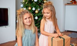 Two sisters with blond hair in luxurious dresses are sitting near the Christmas tree and looking at the gifts. New Year royalty free stock photo