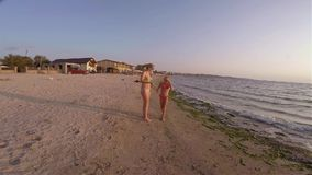 Two sisters of the blonde in a bathing suit are funny dancing on the beach stock video