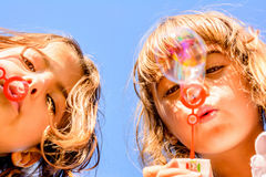 Two sisters blowing bubbles. Two little girls are blowing bubbles in the park Stock Photography