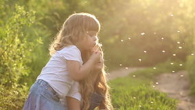 Two sisters blowing a dandelion. Two little sister are blowing on a dandelion. Rest at nature. Slow motion stock video