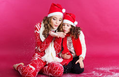 Two sisters are blowing fake snow in studio Stock Image