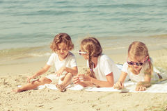 Two sisters and brother playing on the beach Royalty Free Stock Photo