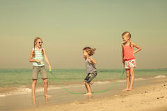 Two sisters and brother playing on the beach. At the day time.  Concept of friendly family Royalty Free Stock Photos
