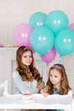 Two sisters are celebrating birthday with cake Royalty Free Stock Photos
