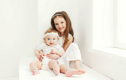 Two sisters children playing together at home. In white room Royalty Free Stock Photo