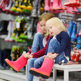 Two sisters choosing and trying on new rain boots Stock Photography