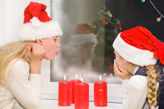 Two sisters at Christmas with candles. Two sisters in a Christmas evening with candles in the window Royalty Free Stock Image