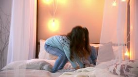 Two sisters at Christmas, jumping on the bed in sweaters, fun, laugh and hug. Two sisters at Christmas, jumping on the bed in sweaters, fun, laugh and hug stock video