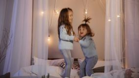 Two sisters at Christmas, jumping on the bed in sweaters, fun, laugh and hug. Two sisters at Christmas, jumping on the bed in sweaters, fun, laugh and hug stock footage