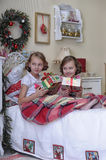 Two sisters on Christmas morning. Two sisters in the morning in bed with Christmas gifts stock image