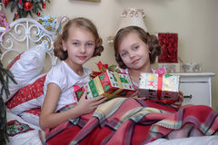 Two sisters on Christmas morning. Two sisters in the morning in bed with Christmas gifts stock photos
