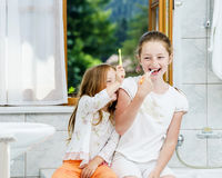 Two sisters cleaning the teeth together Royalty Free Stock Photography