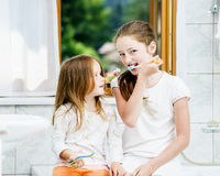 Two sisters cleaning the teeth together Royalty Free Stock Photo