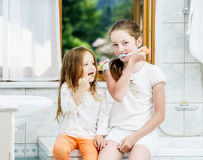 Two sisters cleaning the teeth together Royalty Free Stock Images