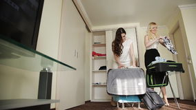 Two sisters collect things in a suitcase in a hotel room. Sisters collect things in a suitcase in a hotel room for a trip to the resort stock video