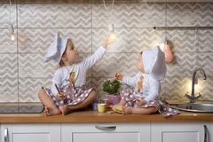 Two sisters in a cook hats sit on the kitchen table and drink tea with cookies