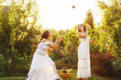 Two sisters and crop. Two cute sisters in long white dresses and a basket with harvest. She catches eggplant. Ripe fruits and vegetables. A bountiful harvest Stock Photography