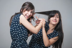 Two sisters cutting their hair with funny faces Royalty Free Stock Image
