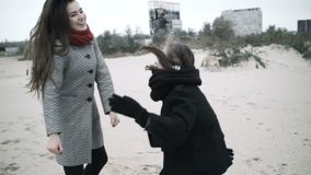 Two sisters dance on the beach. Sisters have fun on a walk. Camera around stock footage