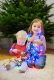 Two sisters decorating Christmas tree Stock Image