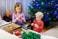 Two sisters decorating Christmas tree Stock Photos