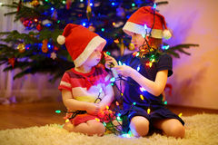 Two sisters decorating Christmas tree Stock Images