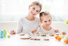 Two Sisters Decorating Gingerbread Cookies On Kitchen Royalty Free Stock Photos