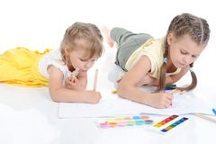 Two sisters draw on the album. Stock Photo