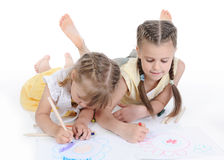 Two sisters draw on the album. Stock Image