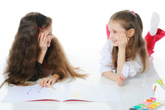 Two sisters draw on the album. Stock Images