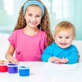 Two sisters draw finger paints Royalty Free Stock Image