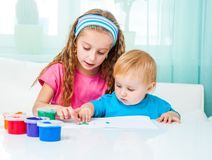 Two sisters draw finger paints Royalty Free Stock Photos